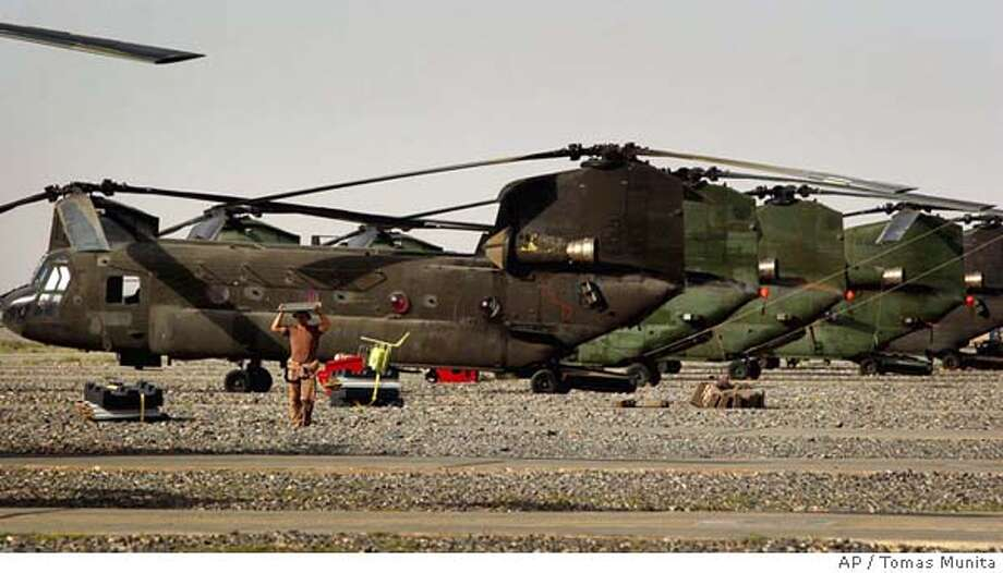 A U.S. soldier performs maintenance of CH-47 Chinook helicopters at Kandahar air field, southern Afghanistan, Wednesday, June 29, 2005. A CH-47 Chinook transport helicopter, carrying 15 to 20 people, crashed Tuesday in while ferrying reinforcements to fight insurgents in a mountainous region in eastern Afghanistan. The Taliban claimed to have shot down the aircraft. (AP Photo/Tomas Munita) Photo: TOMAS MUNITA