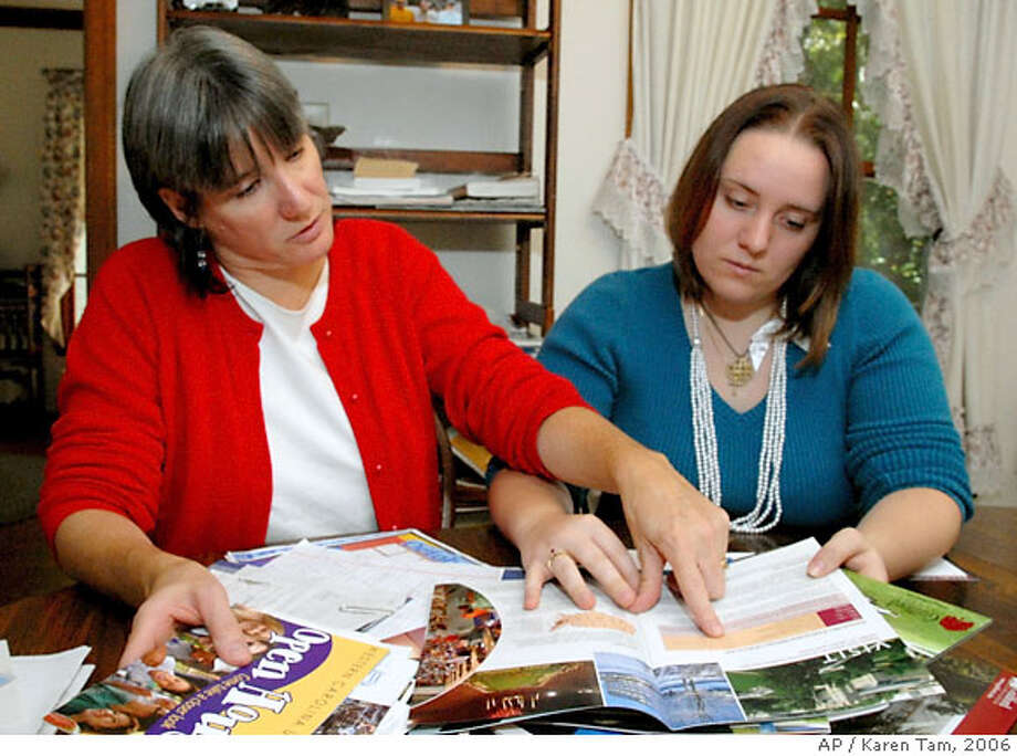 ** ADVANCE FOR SUNDAY, OCT. 22 **Cathy Millward, left, helps her daughter, Caitlin, 18, Sunday afternoon Oct. 15, 2006, go through many of the college brochures they have collected in the past few months in their search for the college Caitlin will attend next fall. (AP Photo/Karen Tam) Photo: KAREN TAM