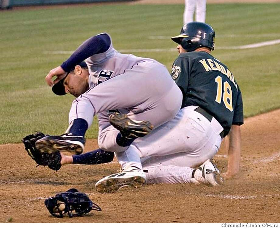 ATHLETICS_069_OHARA.CR2  McAfee Colliseum, Athletics V/S Mariners  Bottom 4th inning.  Moyers pitche gets by the catcher. Jason Kendall goes to home plate from third on the bad pitch. Moyer tries tocover home. Kendall up ends him in his safe slide , to score  photo.......john O'hara Photo: John O'Hara