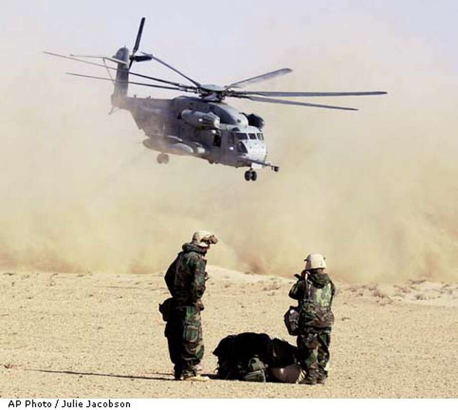 United States Marines CSSG-11 2nd Lt. Douglas Watts, left, of Gretna, La., left, and Staff Sgt. Chia Cha of Fresno, Calif, watch a CH-53E Sea Stallion helicopter take off from a pickup zone in southern Iraq Friday, March 28, 2003. The aircraft, along with several others from the Marines and Air Force, fanned out across Iraq Friday delivering overdue supplies and troops that were held up because of several days of dust and sand storms. (AP Photo/Julie Jacobson) Photo: JULIE JACOBSON