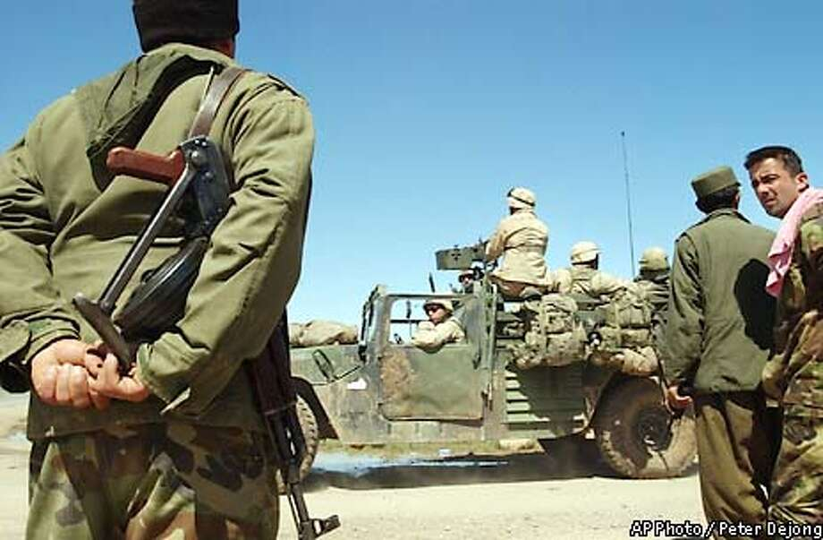 Kurdish fighters watch a convoy of American soldiers with the 173rd Airborne out of Vicenza, Italy, leave from an airstrip near Harir, Kurdish-held northern Iraq, Saturday March 29, 2003. Some 1,000 U.S. soldiers arrived midweek and haved fanned out throughout the region. (AP Photo / Peter Dejong) Photo: PETER DEJONG