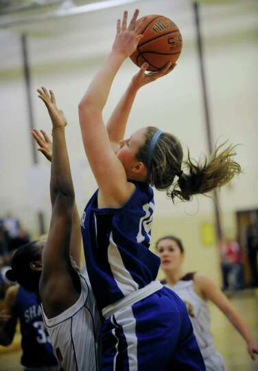 Shaker's Lauren Woods ,right, puts up a shot against Colonie's during their High School Basketball g