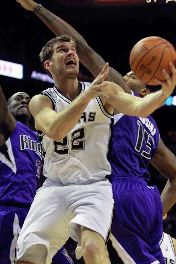 Tiago Splitter reverses under the hoop to score against DeMarcus Cousins as the Spurs play Sacramento at the AT&T Center in San Antonio on January 20, 2012 Tom Reel/ San Antonio Express-News Photo: TOM REEL, Express-News / © 2012 San Antonio Express-News  MAGS OUT; TV OUT; NO SALES; SAN ANTONIO OUT; AP MEMBERS ONLY; MANDATORY CREDIT; EFE OUT