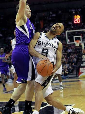Tony Parker, who had 24 points on 8-of-18 shooting and six assists, makes contact with Sacramento's Jimmer Fredette during the first half. Photo: TOM REEL, Express-News / © 2012 San Antonio Express-News  MAGS OUT; TV OUT; NO SALES; SAN ANTONIO OUT; AP MEMBERS ONLY; MANDATORY CREDIT; EFE OUT