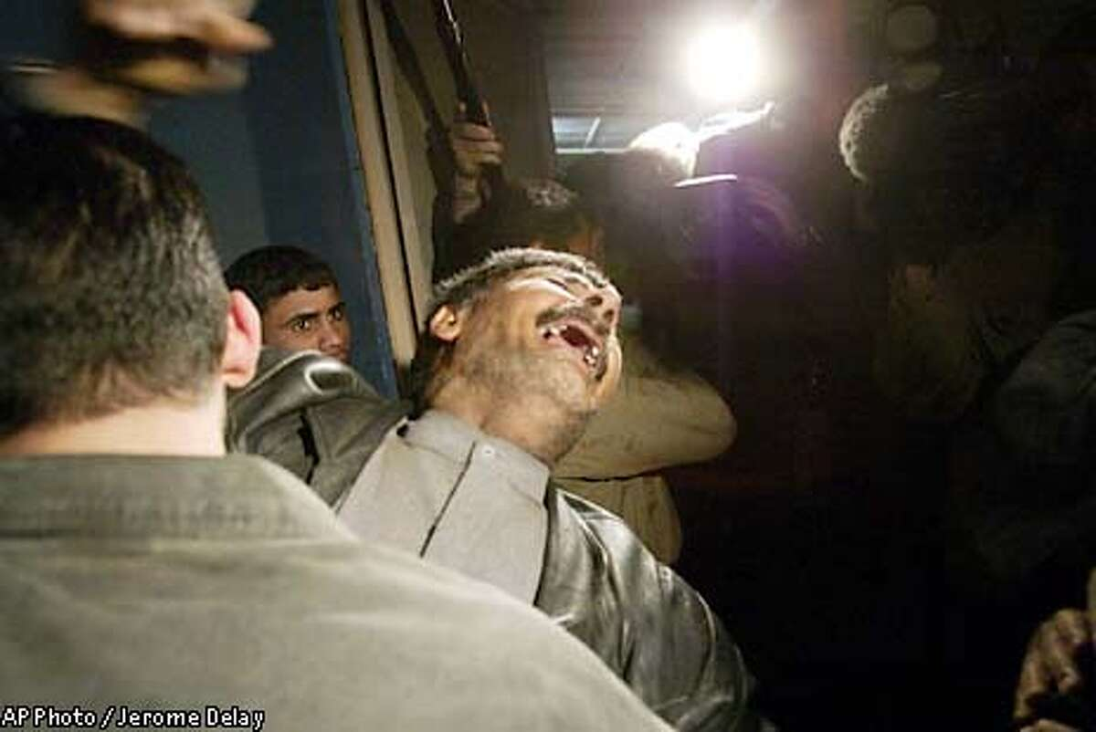 Abdul Hussein cries after seeing his son Heider, 25, dead body in the morgue of Al Nur hospital, following a bomb that landed in a busy market in the Al Shula'a district of West Baghdad Friday March 28 2003. The bomb killed at least 50 people, according to local hospital sources. The U.S. Central Command in Qatar said it was looking into the matter.(AP Photo/Jerome Delay)