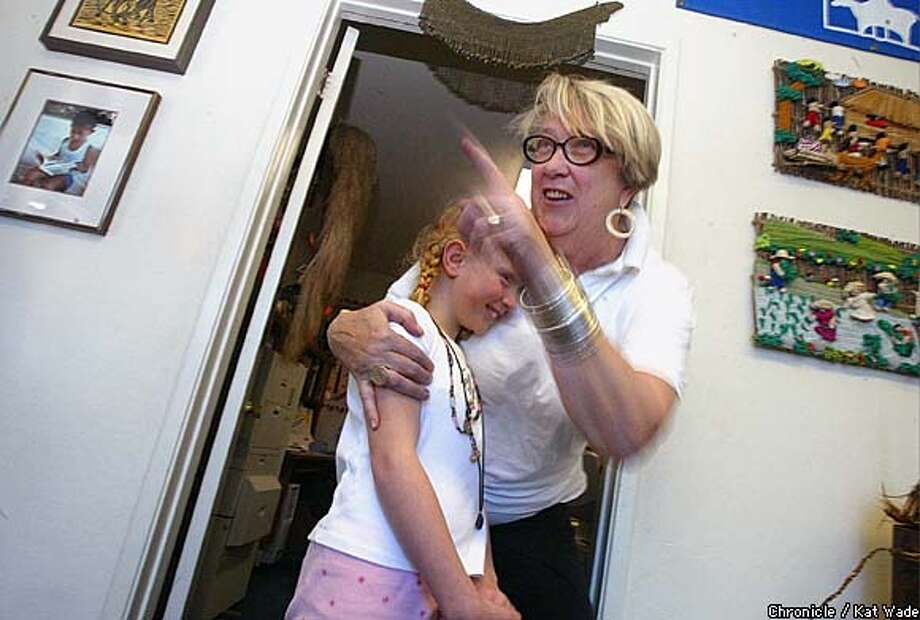 Nancy Harrington, who runs Books for the Barrios, hugs Kelly Sullenberger, who celebrated her 8th birthday by giving the organization books to send to the Philippines. Chronicle photo by Kat Wade