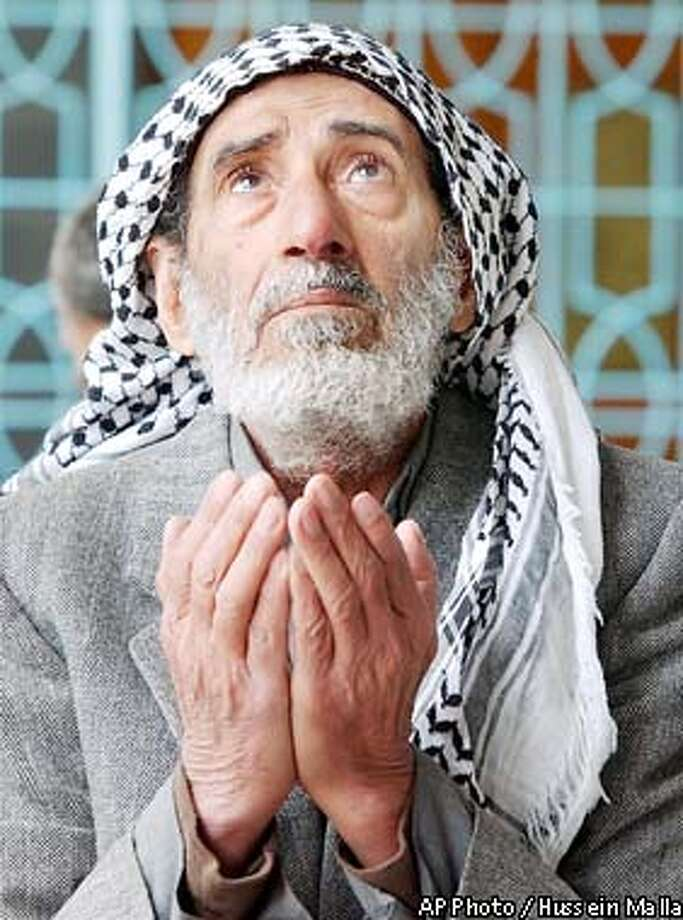 An Iraqi prays at the Muslim shiite shrine of Sayda Zeinab, during prayers in Damascus, Syria, Friday, March 21, 2003, where muslims come to pay homage to the prophet's granddaughter, Zeinab. More than half a million Iraqis are currently in Syria, where they have been arriving in buses and cars over the past month and are now waiting for the war to end to go back to their homes.(AP Photo/Hussein Malla) Photo: HUSSEIN MALLA
