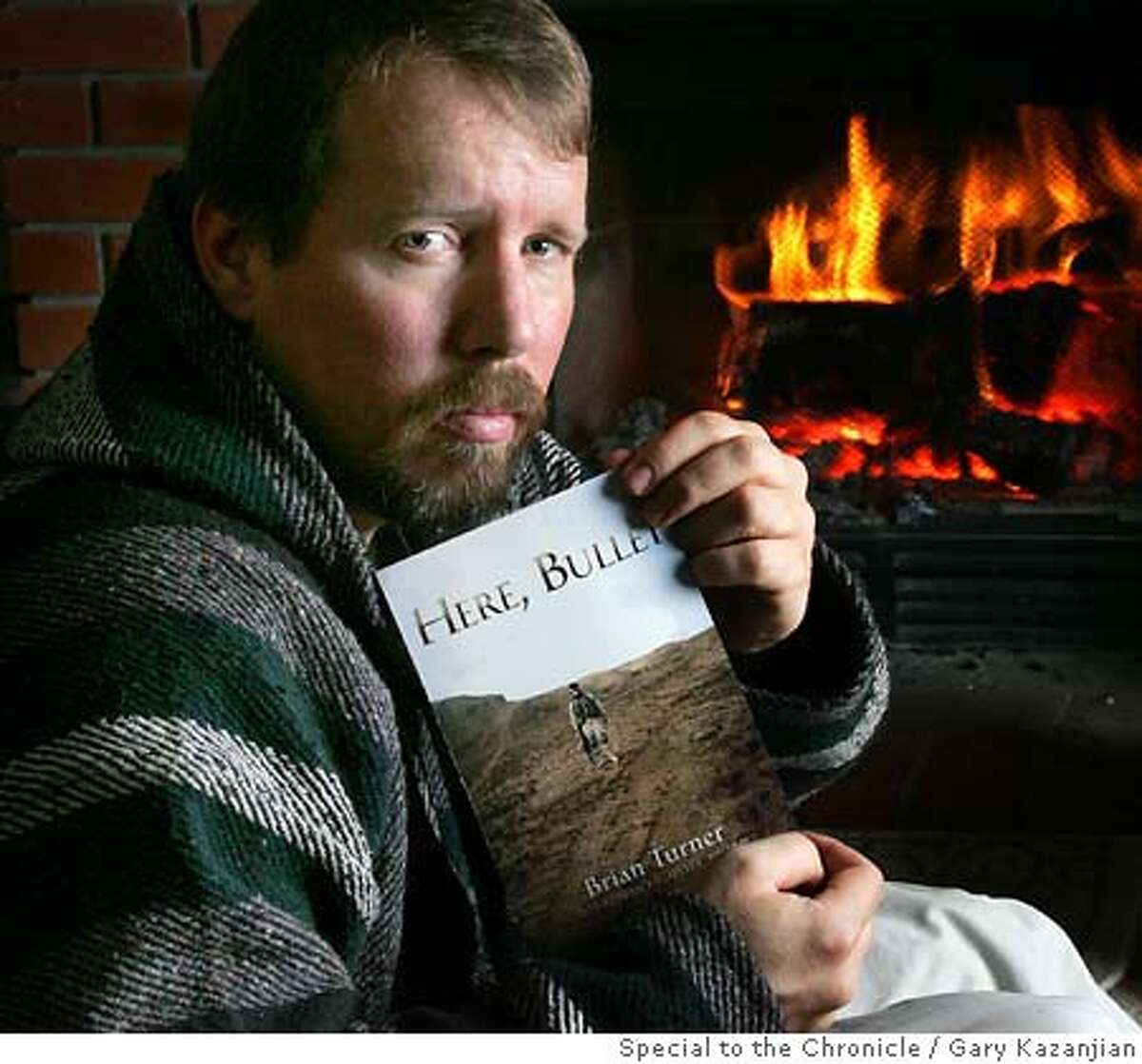 """�Brian Turner, at his home with his book Thursday, Dec. 28, 2006 in Fresno, Calif. Turner is a poet who served seven years in the U.S. Army. He deployed to Bosnia-Herzegovina and spent a year as an infantry leader in Iraq with the 3rd Stryker Brigade Combat Team. He wrote a book of poems about Iraq, """"Here, Bullet,"""" that published to much acclaim. Turner teaches creative writing at Calif. State University, Fresno. . By GARY KAZANJIAN/SPECIAL TO THE CHRONICLE Gary Kazanjian"""
