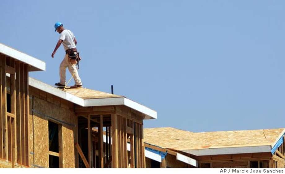 A construction worker walks the roof of a new housing development in San Jose, Calif. on Monday, Aug. 21, 2006. Construction spending fell in September as home building declined for a sixth consecutive month, the longest stretch of weakness in residential construction in more than a decade. (AP Photo/Marcio Jose Sanchez)  Ran on: 11-18-2006  This development in San Jose is one of a few being built in recent months as construction activity continues to stagnate.  Ran on: 01-05-2007  New homes, like this development in San Jose, will be built at about the same rate as they were last year, a trade group predicts. It does not expect deep price cuts. Photo: MARCIO JOSE SANCHEZ