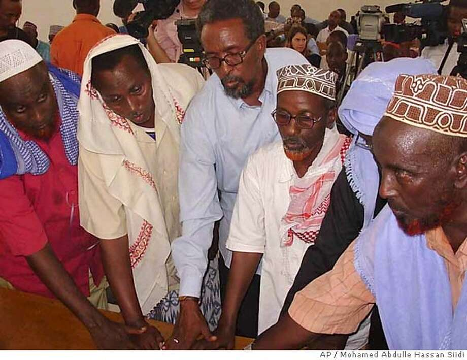 """Transitional Federal Government Banadir court officials put their hands on the Holy Quran during a swear in ceremony in Mogadishu, Somalia, Thursday, Jan. 4, 2007. Remnants of Somalia's Islamic movement still pose a threat in the capital, the interior minister said Thursday, days after his government's and Ethiopian troops chased most of the militiamen from Mogadishu. """"There are 3,500 Islamists hiding in Mogadishu and the surrounding areas and they are likely to destabilize the security of the city,"""" Interior Minister Hussein Aideed told journalists at a news conference. (AP Photo/Mohamed Abdulle Hassan Siidi)) Photo: MOHAMED ABDULLE HASSAN SIIDI"""