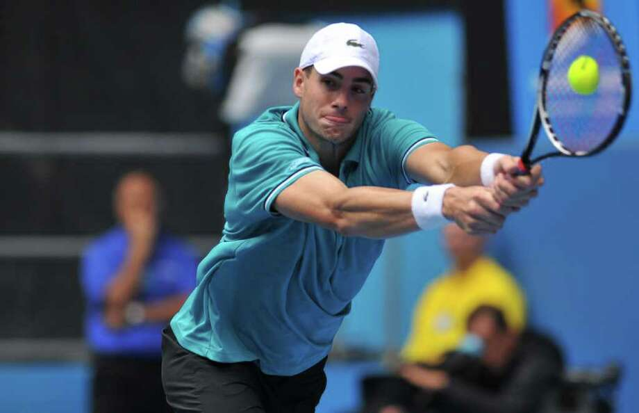 John Isner uses his 6-9 frame to reach a return against Feliciano Lopez of Spain in third-round action. Isner lost in five sets, leaving no American men in singles. Photo: NICOLAS ASFOURI / AFP