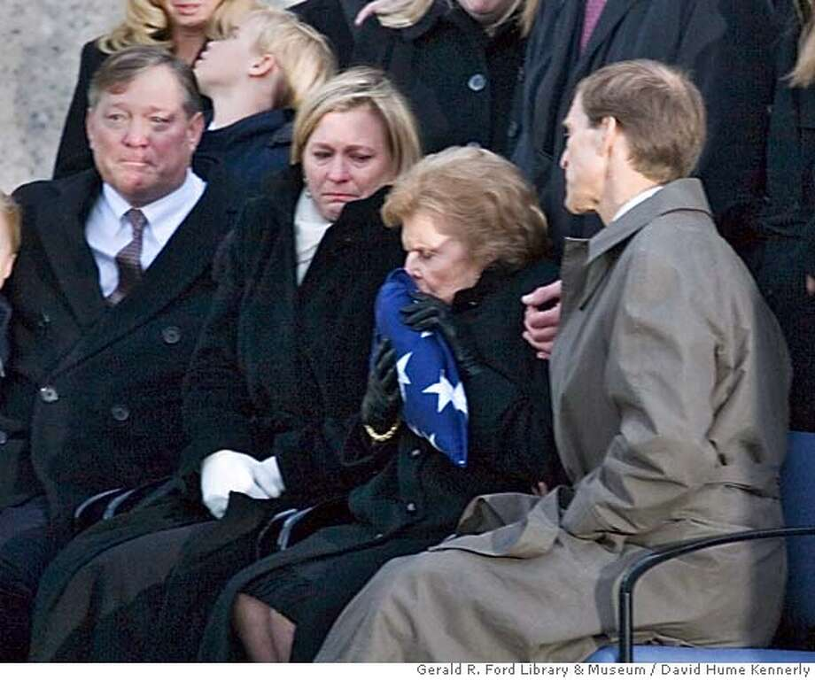 In this photo provided by the Gerald R. Ford Library & Museum, former first lady Betty Ford kisses the flag that draped former President Gerald Ford's casket after interment ceremonies at the Gerald R. Ford Presidential Museum on Wednesday, Jan. 3, 2007, in Grand Rapids, Mich. (AP Photo/Gerald R. Ford Library & Museum, David Hume Kennerly) ** PHOTO PROVIDED BY THE GERALD R. FORD LIBRARY & MUSEUM ** Photo: David Hume Kennerly
