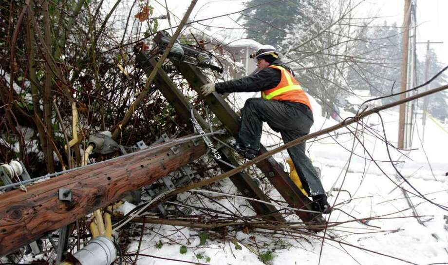 Derrick Lonneker climbs up a downed power pole, as he works to repair a transmission line damaged by a falling tree near a substation, Friday, Jan. 20, 2012, in Olympia, Wash. Heavy layers of ice brought down trees and power lines across the Northwest Friday, following two days of snow and ice storms and crews will be busy through the weekend restoring power. Photo: Ted S. Warren / Associated Press
