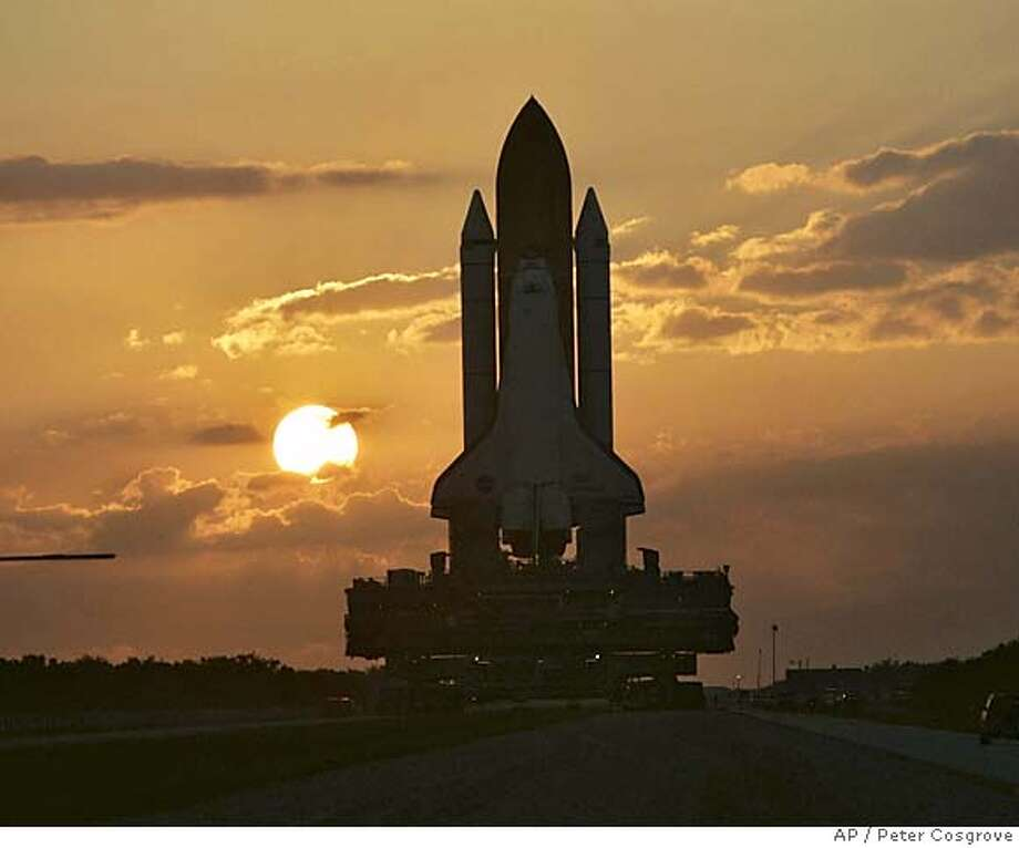 The space shuttle Discovery moves slowly toward the pad as the sun rises at Kennedy Space Center in Cape Canaveral, Fla. Wednesday, June 15, 2005. Discovery is scheduled for launch no earlier than July 13, 2005. (AP Photo/Peter Cosgrove) Photo: PETER COSGROVE
