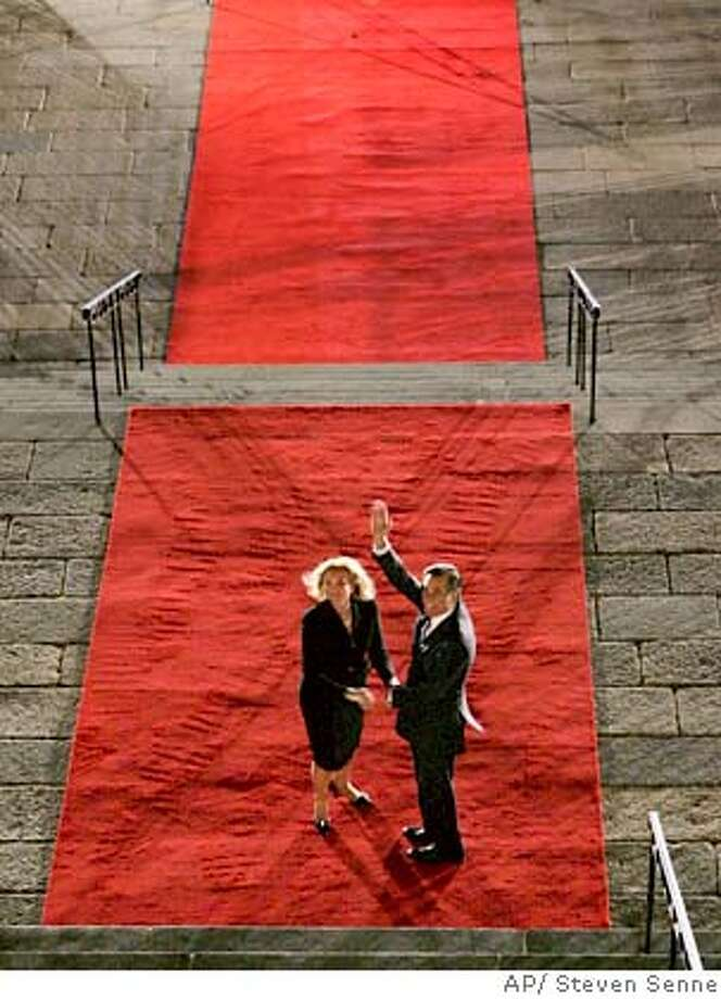 """Outgoing Massachusetts Gov. Mitt Romney, right, and his wife Ann turn to wave from the red carpet in front of the Statehouse, in Boston, as Romney completes the """"lone walk"""" out of the Statehouse, Wednesday, Jan. 3, 2007. Deval Patrick will be sworn in as the new governor on Thursday. (AP Photo/Steven Senne) Photo: Steven Senne"""