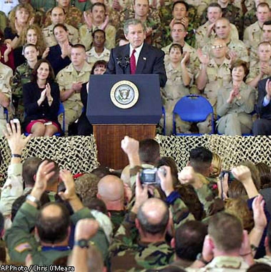** RETRANSMISSION FOR ALTERNATE CROP ** President Bush draws applause from the troops stationed at MacDill Air Force Base during a speech Wednesday morning March 23, 2003 in Tampa, Fla. MacDill Air Force Base is the home to the United States Central Command. First Lady Laura Bush, and Florida Governor Jeb Bush, right, look on. (AP Photo / Chris O'Meara) Photo: CHRIS O'MEARA