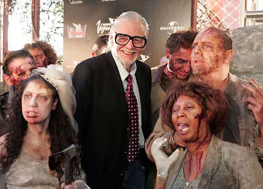 """Legendary horror picture film director George A. Romero poses on the red carpet with zombie's just before the premiere of his latest motion picture, """"Land of The Dead"""", during , Saturday, June 18, 2005 at the Palms Hotel and Casino in Las Vegas. Romero is generally considered to be the father of modern horror film and is known for such films as, """"Night of The Living Dead"""", """"Dawn of the Dead"""" & """"Bruiser"""". (AP Photo/Eric Jamison) Photo: ERIC JAMISON"""