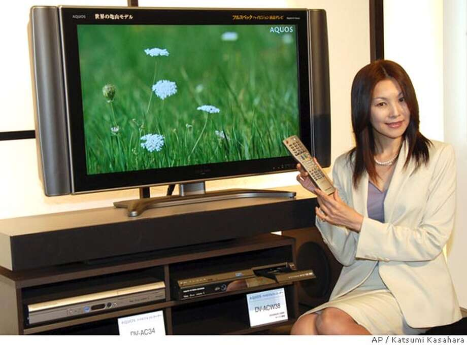 """A model displays the new Sharp Corp.'s Aquos liquid-crystal display TV during a news conference in Tokyo Wednesday, Aug. 2, 2006. The new flat-panel TV is called """"Kameyama model,"""" made at a newly built 150 billion yen (US$1.3 billion; euro1 billion) plant in Kameyama, central Japan. Manufacturers making flat panels are tackling a supply problem, but what kind of problem depends on where the company stands on the electronics-brand totem pole. (AP Photo/Katsumi Kasahara) Photo: KATSUMI KASAHARA"""