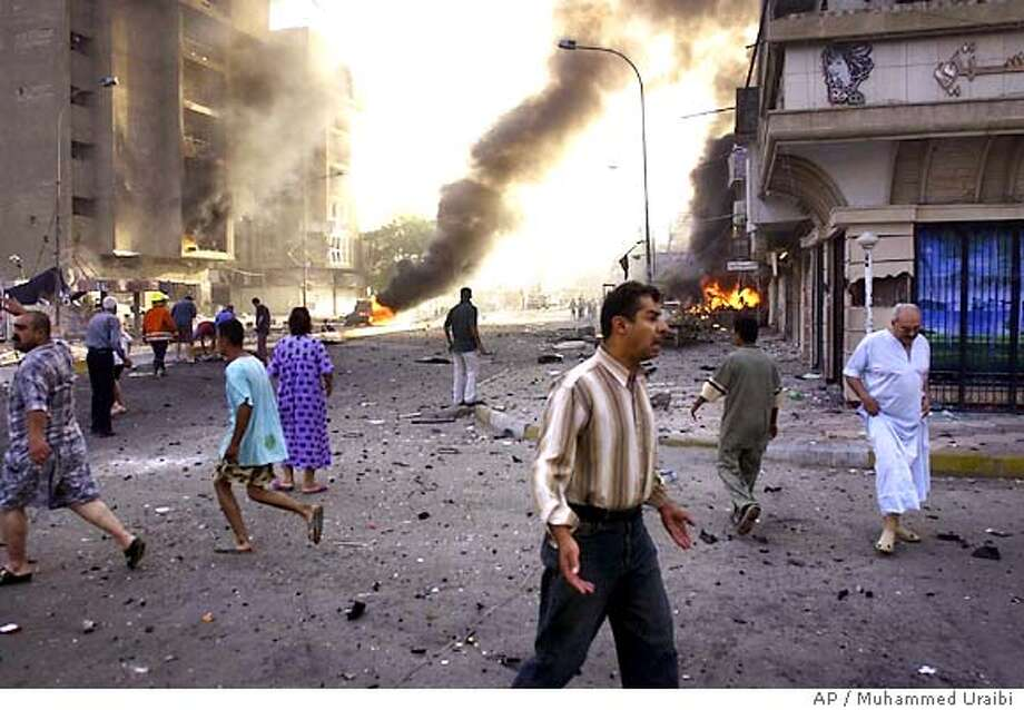 Iraqis search for the victims Thursday, June 23, 2005 in Baghdad. At least two car bombs exploded just after dawn Thursday in Baghdad's middle-class Karada area, a central shopping district. Police reported casualties but had no details. (AP Photo/Muhammed Uraibi) Photo: MUHAMMED URAIBI