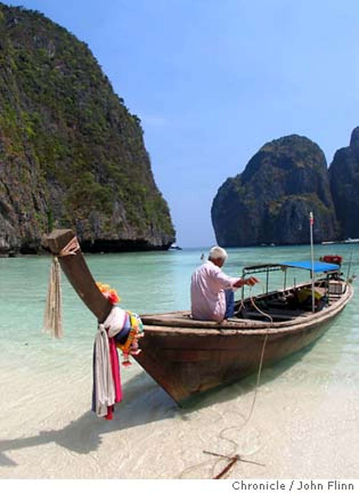 TRAVEL THAILAND -- A traditional Thai long-tail boat pulls up to the beach on Phi Phi Leh island. The uninhabited island, where scenes for