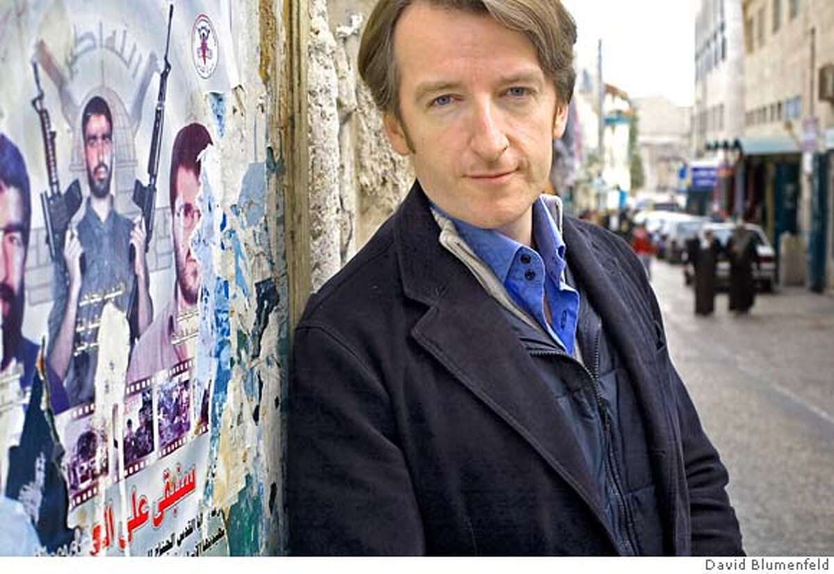 """Bethlehem, West Bank: Matt Beynon Rees, writer of """"The Collaborator of Bethlehem,"""" his first novel in a new mystery series photographed next to a Martyr's poster in Bethlehem. �David Blumenfeld"""
