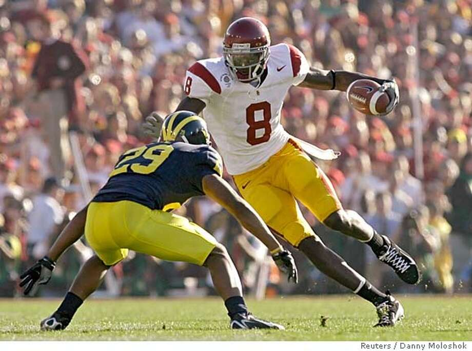 USC Trojans Dwayne Jarrett (8) gets the first down as he approaches the Michigan Wolverines cornerback Leon Hall in the first quarter of the 93rd Rose Bowl game in Pasadena, California, January 1, 2007. REUTERS/Danny Moloshok (UNITED STATES) Photo: DANNY MOLOSHOK