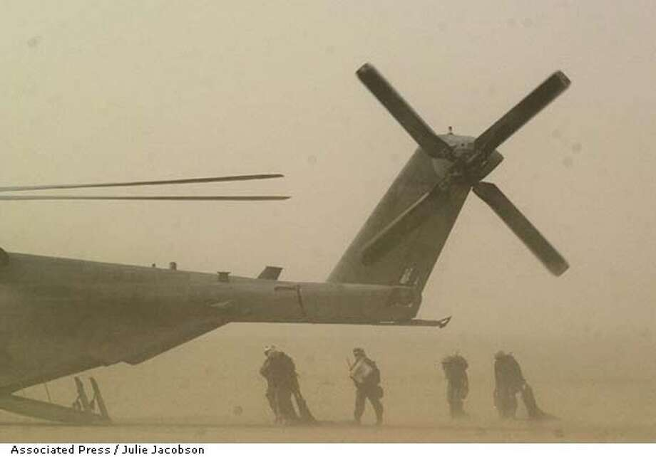 United States Marines from the 1st Forward Services Support Group make their way through a sand storm to board a CH-53E Sea Stallion in the Kuwaiti desert while on a mission to help resupply troops in Iraq with ammunition and equipment Tuesday, March 25, 2003. Shortly after takeoff, the mission was turned back because of bad weather which included blowing sands, visibility of one and a half miles and wind gusts of up to 40 miles per hour. (AP Photo/Julie Jacobson) Photo: JULIE JACOBSON