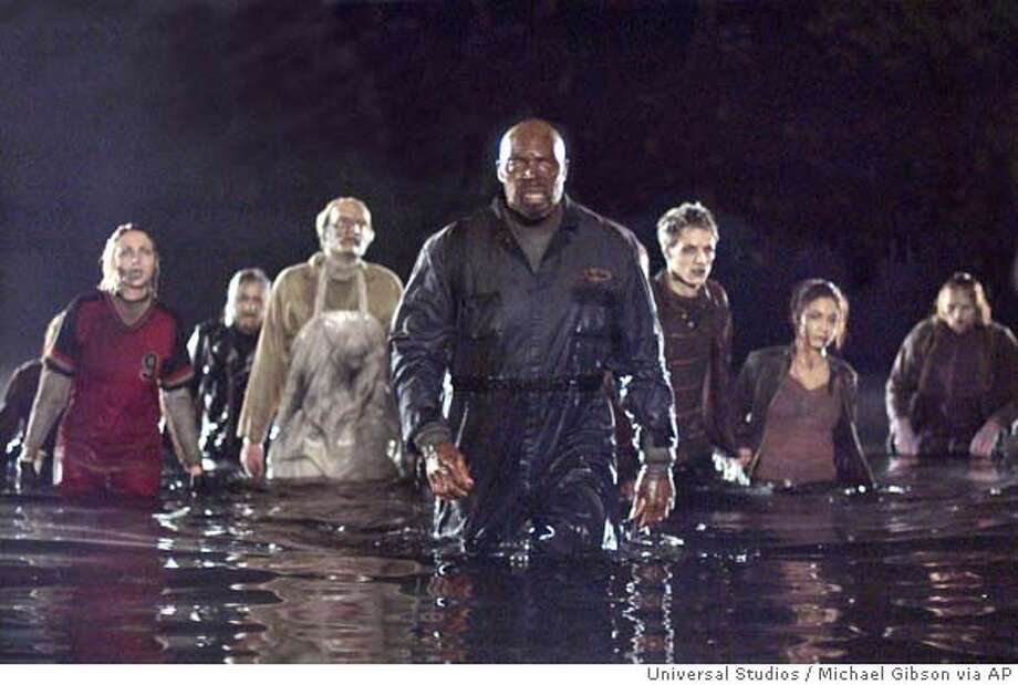 "In this photo provided by Universal Studios, Zombie Big Daddy (Eugene A. Clark, center) leads a growing and evolving horde of the dead in their attack on the city of the living in "" Land of the Dead."" (AP Photo/Universal Studios/Michael Gibson) Photo: MICHAEL GIBSON"