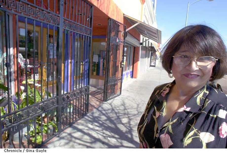 OAKLAND26a-C-25MARO3-MT-GG - Oakland business owner Josefina Lopez stands outside her store on International Blvd and looks down the street. Josefina has attractive gates around ehr door and windows as protection from burgleries and crime. Photo by GINA GAYLE/THE SAN FRANCISCO CHRONICLE.  Byline