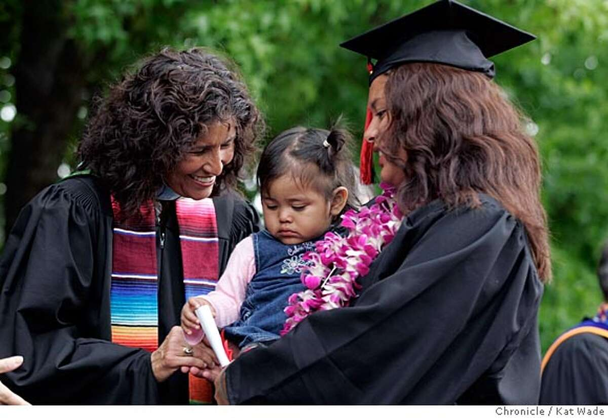 On 6/16/05 in Redwood City Predident of Ca�ada College, Rosa Perez smiles at Gabrielle Ramos, 14 mos., after her mother Leslie Ramos got her G.E.D. durrng the graduation ceremony at Redwood High School today. Pregnant teen, teen mothers like Ramos, participated in a San Mateo County Department of Social Services program graduate at , with the help of parenting classes, and GED lessons. Kat Wade/ The Chronicle