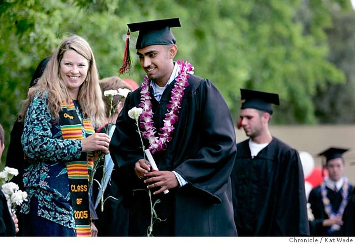 On 6/16/05 in Redwood City Safe Place counselor, Evelyn Hall smiles at teen father Genaro Lombera after he got his diploma durrng the graduation ceremony at Redwood High School today. Pregnant teen, teen mothers and fathers like Lombera, participated in a San Mateo County Department of Social Services program graduate at , with the help of parenting classes, and GED lessons. Kat Wade/ The Chronicle