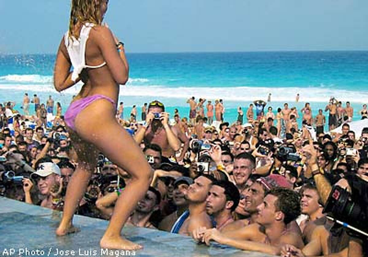 A young American woman dances before the students during a wet T-shirt contest Thursday, March 20, 2003, in Cancun, Mexico.