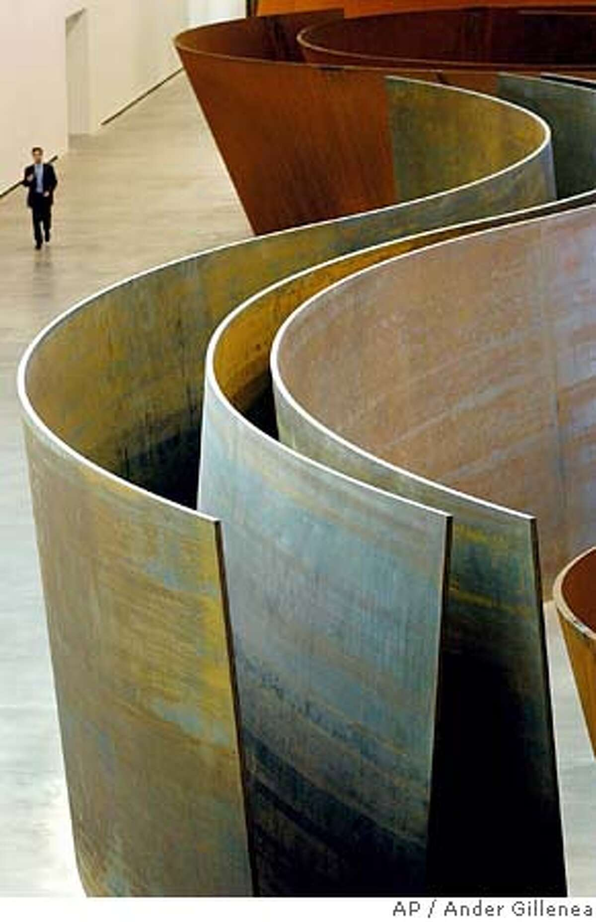 A person walks past a steel sculpture made by U.S. artist Richard Serra at the Guggenheim museum in Bilbao, Spain, Tuesday, June 7, 2005. The exhibition titled 'The matter of Time' will be opened to the public on Wednesday. (AP Photo/Ander Gillenea) EFE OUT