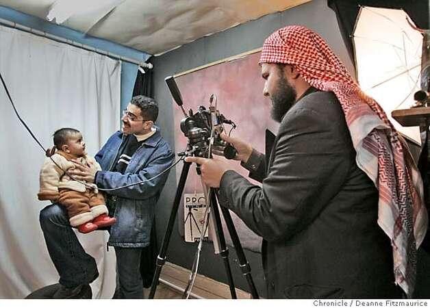 A photo assistant holds baby Ali, 6 months old, as he gets his passport photo taken at a photo studio in Amman, Jordan before getting their visas to come to the United States. Hadia Khanfoosh and her children flee Iraq and come to America to join her son, Saleh, and her husband, Raheem after being apart for over a year. Through an international medical intervention, Saleh Khalaf, 10, on the brink of death after a bomb explosion, was brought from Iraq to Oakland Children's Hospital along with his father, Raheem in November 2003. They were granted political asylum when it became unsafe for them to return to Iraq. Deanne Fitzmaurice / The Chronicle Photo: Deanne Fitzmaurice