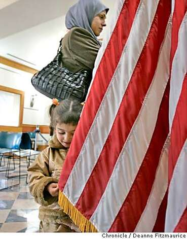 Mawra, 3, plays with the American flag while Hadia stands at the window of the U.S. Embassy in Amman, Jordan to get visas to go to the United States. Hadia Khanfoosh and her children flee Iraq and come to America to join her son, Saleh, and her husband, Raheem after being apart for over a year. Through an international medical intervention, Saleh Khalaf, 10, on the brink of death after a bomb explosion, was brought from Iraq to Oakland Children's Hospital along with his father, Raheem in November 2003. They were granted political asylum when it became unsafe for them to return to Iraq. Deanne Fitzmaurice / The Chronicle Photo: Deanne Fitzmaurice
