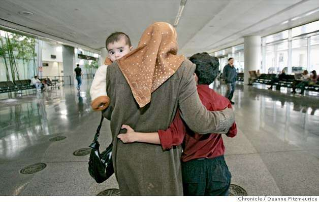 Saleh Khalaf puts an arm around his mother, Hadia as they walk through San Francisco International Airport. Baby Ali, 6 months old looks over her shoulder. Hadia Khanfoosh and her children fled Iraq and came to America to join her son, Saleh, and her husband, Raheem after being apart for over a year. Through an international medical intervention, Saleh Khalaf, 10, on the brink of death after a bomb explosion, was brought from Iraq to Oakland Children's Hospital along with his father, Raheem in November 2003. They were granted political asylum when it became unsafe for them to return to Iraq. Deanne Fitzmaurice / The Chronicle Photo: Deanne Fitzmaurice