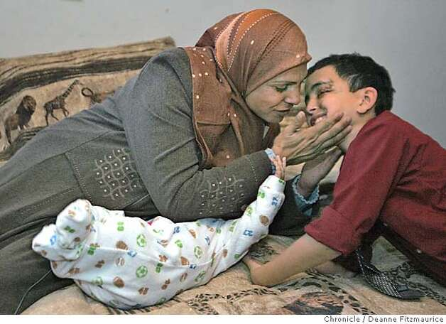 Hadia kisses her son, Saleh, once they arrive back at their Oakland apartment on the day she arrives from Iraq. Ali, 6 months old, reaches up to them. Hadia Khanfoosh and her children flee Iraq and come to America to join her son, Saleh, and her husband, Raheem after being apart for over a year. Through an international medical intervention, Saleh Khalaf, 10, on the brink of death after a bomb explosion, was brought from Iraq to Oakland Children's Hospital along with his father, Raheem in November 2003. They were granted political asylum when it became unsafe for them to return to Iraq. Deanne Fitzmaurice / The Chronicle Photo: Deanne Fitzmaurice
