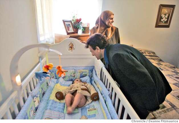 Raheem puts baby Ali, 6 months old into his brand new crib at their apartment in Oakland on the day his wife and children arrive from Iraq. Hadia Khanfoosh and her children flee Iraq and come to America to join her son, Saleh, and her husband, Raheem after being apart for over a year. Through an international medical intervention, Saleh Khalaf, 10, on the brink of death after a bomb explosion, was brought from Iraq to Oakland Children's Hospital along with his father, Raheem in November 2003. They were granted political asylum when it became unsafe for them to return to Iraq. Deanne Fitzmaurice / The Chronicle Photo: Deanne Fitzmaurice
