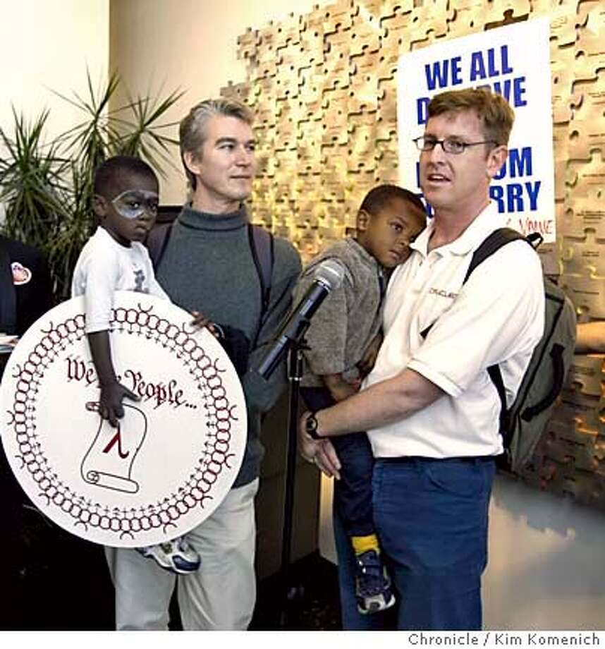 SAMESEX_LOCAL_057_kk.jpg  L to R, Stuart Gaffney and John Lewis of San Francisco (tuxes)) who were married 2/12/04, listen to Olivier DeWulf (holding Laurent Boulianne-DeWulf, 4) and Steven Boulianne, speaking at microphone (holding Reece Boulianne-DeWulf, 3), talk about the failure of the legislation and what it means to same sex couples.  Folks at San Francisco's Lesbian Gay Bisexual Transgender Community Center celebrate the Senate defeat of the proposed federal marriage amendment.  Photo by Kim Komenich in San Francisco MANDATORY CREDIT FOR PHOTOG AND SF CHRONICLE/ -MAGS OUT Photo: Kim Komenich