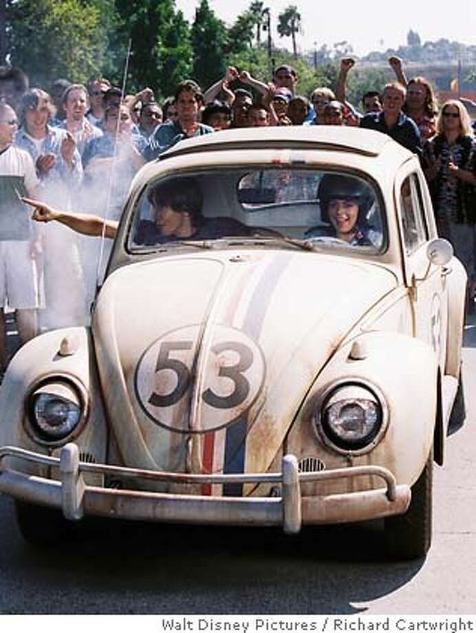In this photo provided by Walt Disney Pictures, Justin Long (left), Lindsay Lohan (right) takes a ride in Herbie, a Volkswagen Bug that can drive itself, in 'Herbie Fully Loaded' (AP Photo/Walt Disney Pictures/ Richard Cartwright) Photo: RICHARD CARTWRIGHT
