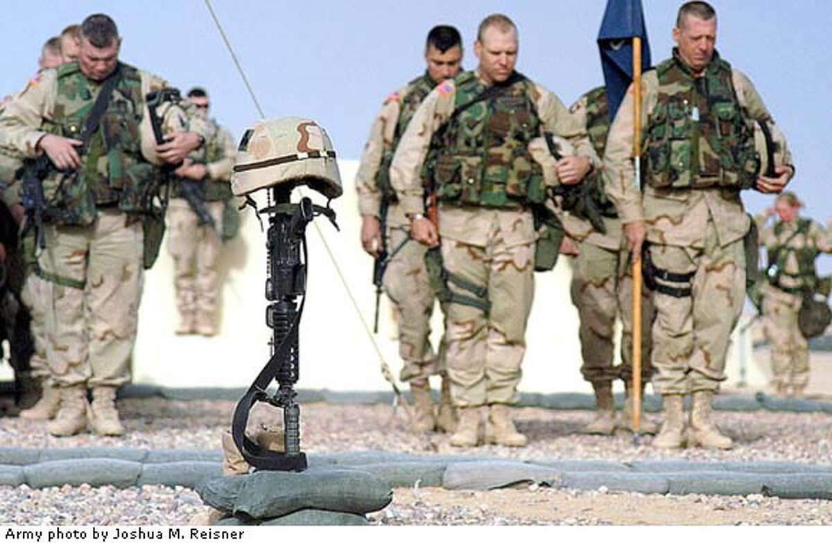 Soldiers of 1st Brigade, 101st Airborne Division (Air Assault), mourn the loss of Capt. Christopher Seifert at a memorial ceremony, Monday, March 24, 2003, at Camp Pennsylvania in Kuwait. Seifert was killed when a grenade was thrown into a sleep tent early Sunday morning by a fellow U.S. soldier. The attack left 15 other soldiers wounded. (AP Photo/U.S. Army, Spc. Joshua M. Reisner, pool)