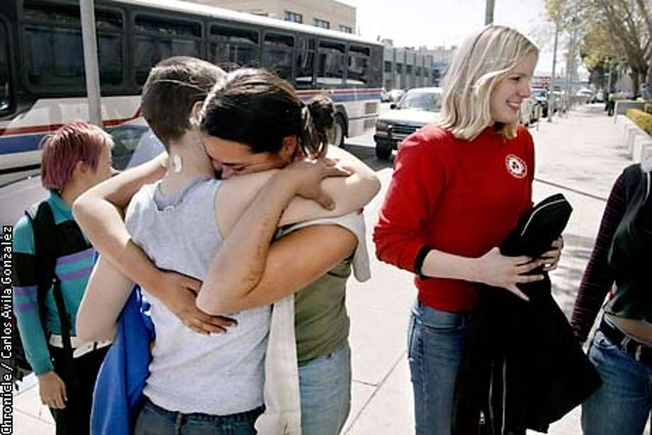 """Jane Doe #1 hugs Jane Doe #2 as Jane Doe #3, right, looks on in front to the San Francisco, Ca., Hall of Justice after they were all released on Friday, March 21, 2003. All had been arrested the day before during protests in San Francisco, but had refused to give names to authorities and were charged as """"Janes Doe"""" before being released.  (Photo by Carlos Avila Gonzalez/The San Francisco Chronicle) Photo: CARLOS AVILA GONZALEZ"""