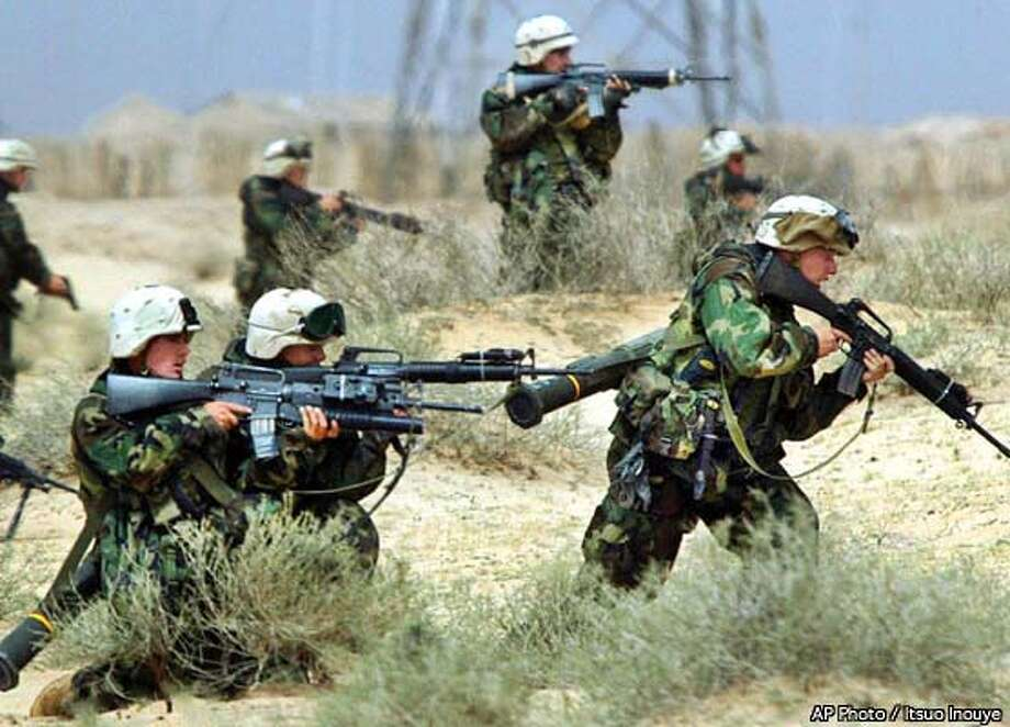 U.S. Marines from the 15th Marine Expeditionary Unit, take firing position hearing the sound of gunfire in southern Iraq Friday, March, 21, 2003. AP Photo / Itsuo Inouye Photo: ITSUO INOUYE
