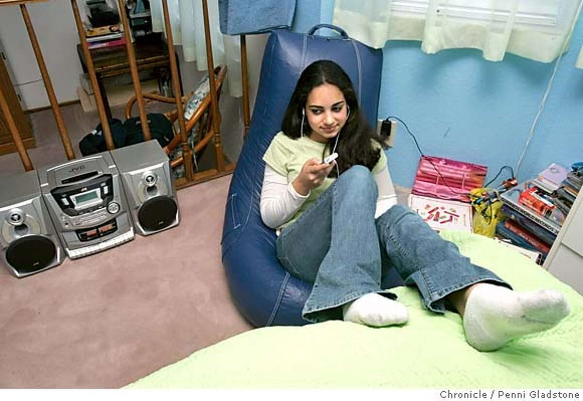 iPOD27010PG.JPG listening to music with her iPod on this comfy chair in her room San Ramon eighth grader Peggah Elahi, 13, saved up months of allowance and baby sitting money so she could buy a $250 iPod Mini. The San Francisco Chronicle, Penni Gladstone Photo taken on 12/21/04, in San Ramon, CA.