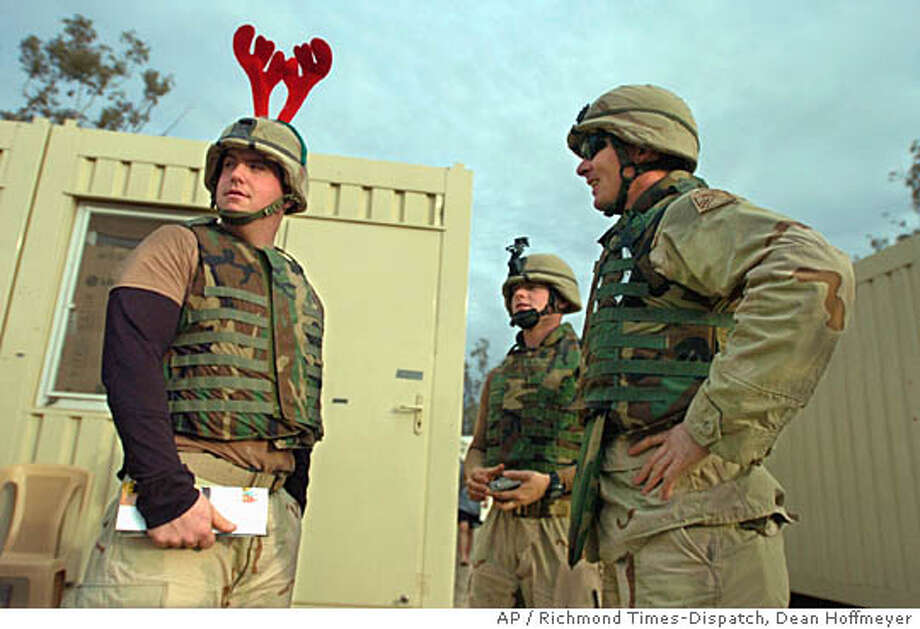 Spc. Seth White of Marion, Va., wears reindeer antlers on his helmet as Sgt. Eric Wagner of North Carolina, center, and Staff Sgt. Tommy Quigley of Hopewell, Va., talk outside their living quarters on Forward Operating Base Marez, Friday, Dec. 24, 2004 in Mosul, Iraq. With high security at the base after Tuesday's bombing, soldiers have been a bit somber in their celebration of the holidays, with flashes of levity to lighten the mood. (AP Photo/ Richmond Times-Dispatch, Dean Hoffmeyer) NOT FOR USE IN DOMESTIC NEWS MAGAZINES; U.S. NEWS & WORLD REPORT OUT; TIME OUT; NEWSWEEK OUT; Photo: DEAN HOFFMEYER