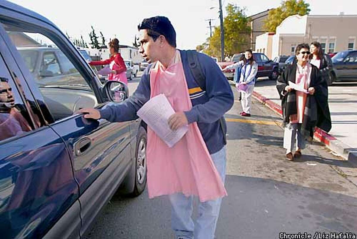 Jimmy Lopez (wearing a pink slip), teacher at Dover Elementary in San Pablo handing out information to parents dropping off their kids. He as well as other teachers who have gotten