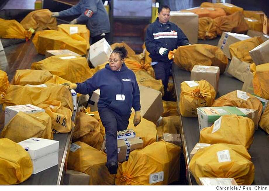 Sorters organize mountains of US Postal Service packages. USPS is Federal Express' largest client. The Federal Express sorting facility at Oakland International Airport on 12/17/04 in Oakland, CA. PAUL CHINN/The Chronicle MANDATORY CREDIT FOR PHOTOG AND S.F. CHRONICLE/ - MAGS OUT Photo: PAUL CHINN