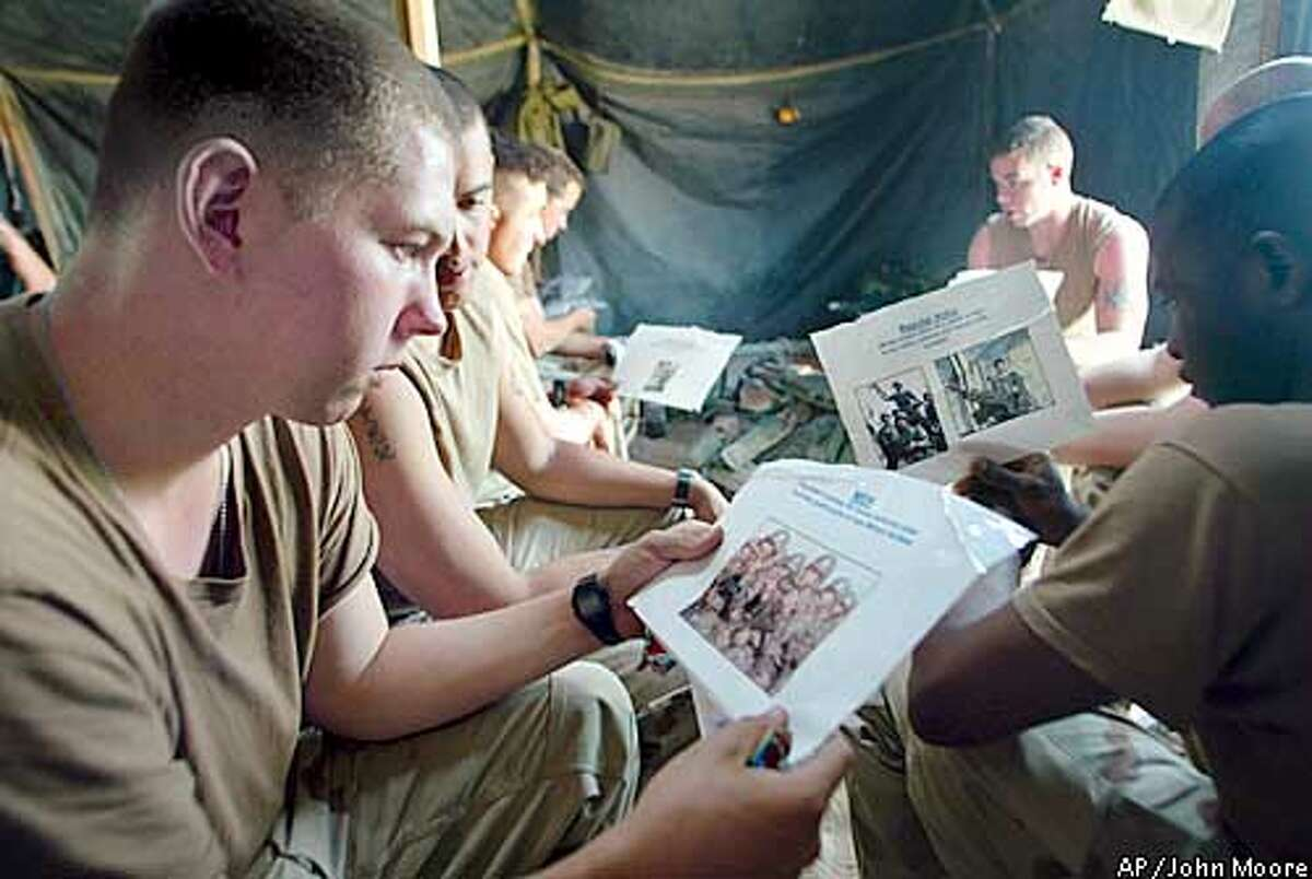 U.S. Army infantrymen from the A Company 3rd Battalion 7th Infantry Regiment, including Spc. Jaime Tielbar, 20, from Waukon, Iowa, left, are briefed on Iraqi forces during a squad-level meeting at their encampment in the desert of western Kuwait Monday, March 17, 2003. U.S. forces are awaiting orders for possible war with Iraq.(AP Photo/John Moore)