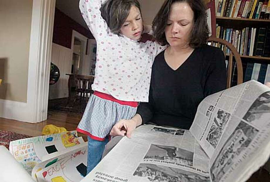 Alice Cannan and her daughter Emily Meymand, 6, look over the Peace coverage in Sunday'smorning paper March 16, 2003 in their Berkeley home. Phil Meymand and his wife, Alice Cannan, are a non-radical, well educated couple who both grew up pretty middle of the road. but recent events have prompted them to join the ranks of anti-war activists in the Bay Area. SAN FRANCISCO CHRONICLE PHOTO BY KAT WADE Photo: KAT WADE