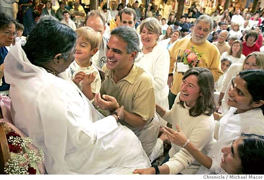 "gurus_014_mac.jpg The Metaxas family of Berkely, Satchi 3, and Van Metaxas and Maria Grayson-Metaxas greet Mata. Reputed as a tireless humanitarian, Mata Amritanandamayi, better known as ""Amma"" or ""Ammachi,"" visits the Bay Area from June 7-19, where she will receive thousands with her blessing-a healing embrace. Free public programs take place at the MA Center on 10200 Crow Canyon Road in San Ramon. Considered a living Saint in her homeland, Amma, 51, has quietly gained an extraordinary reputation over the last 30 years as a result of the extensive charity institutions she has established, and for her personal outreach. Sleeping merely a couple hours per day, she teaches by the constant example of her own life, emphasizing selfless social service. 6/8/05 San Ramon, Ca Michael Macor / San Francisco Chronicle Mandatory Credit for Photographer and San Francisco Chronicle/ - Magazine Out Photo: Michael Macor"